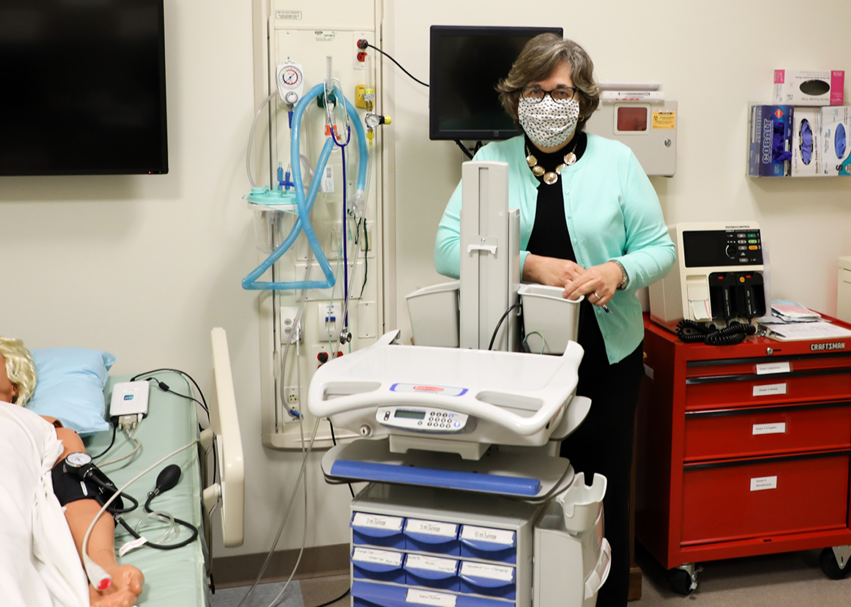Mary Jo Ardis stands in front of a donation to the school from McLeod Health